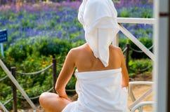 毛巾的一名妇女坐大阳台的一个休息室 免版税库存图片