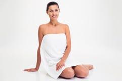 毛巾的微笑的美丽的妇女坐地板 图库摄影