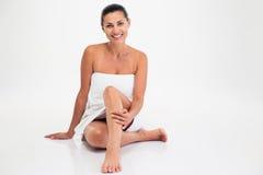 毛巾的微笑的逗人喜爱的妇女坐地板 免版税图库摄影