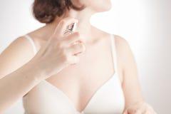 毛巾的美丽的女孩使用香水 免版税库存照片