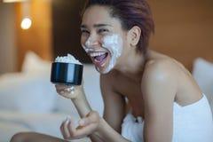 毛巾的美丽的妇女在与打好的奶油的床饮用的咖啡 免版税库存图片