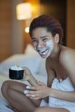 毛巾的美丽的妇女在与打好的奶油的床饮用的咖啡 图库摄影