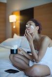 毛巾的美丽的妇女在与打好的奶油的床饮用的咖啡 免版税库存照片
