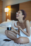 毛巾的美丽的妇女在与打好的奶油的床饮用的咖啡 库存图片