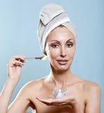 毛巾的美丽的妇女投入奶油 图库摄影