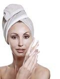 毛巾的美丽的妇女投入奶油 免版税库存图片