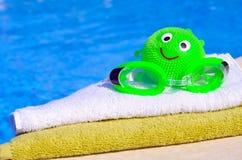 毛巾,风镜,反对大海的玩具 免版税库存图片