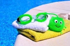 毛巾,风镜,玩具agains蓝色wate 免版税库存照片