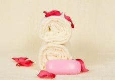毛巾滚动,肥皂,装饰用桃红色瓣 免版税图库摄影