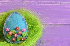 毛毡与塑料花和叶子的复活节彩蛋装饰品 毛毡鸡蛋在巢和在有拷贝空间的紫色木板 免版税图库摄影