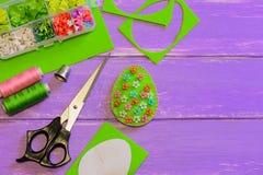 毛毡与塑料花和小珠的复活节彩蛋装饰 毛毡蛋工艺,剪刀,螺纹,纸模板 库存照片