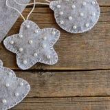 毛毡做的圣诞节装饰品 用小珠由毛毡制成和装饰的圣诞树玩具 葡萄酒木背景 免版税库存图片