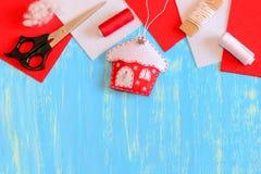 毛毡圣诞树房子装饰品,剪刀,红色和白色螺纹,毛毡编结,在蓝色木背景的补白 图库摄影
