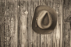 毛毡在土气谷仓墙壁上的牛仔帽 库存图片