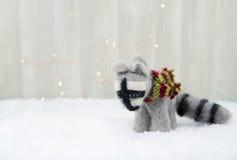 毛毡在雪的浣熊装饰品 免版税库存照片