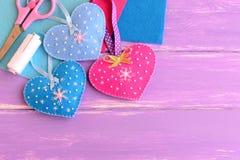 毛毡用小珠和雪花装饰的心脏工艺,剪刀,螺纹,针,在淡紫色木背景的毛毡板料 库存照片