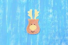 毛毡的缝合的圣诞节驯鹿装饰 步骤 灰棕色感觉在蓝色木背景的驯鹿装饰 库存图片