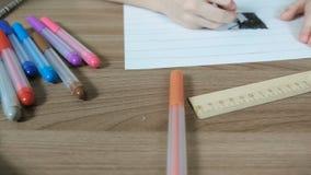 毛毡笔、纸、统治者在桌上和图画男孩` s递特写镜头 照相机移动从左到右 影视素材