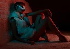 毛皮夹克佩带的面具的性感的女孩 免版税库存图片