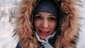 毛皮敞篷的年轻美女谈话在录影连接和走在冬天城市公园的在多雪的天与落 股票录像