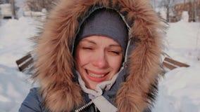 毛皮敞篷的年轻美女谈话在录影连接和走在冬天城市公园的在多雪的天与落 影视素材