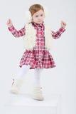 毛皮耳机和背心的小女孩跳舞 免版税库存照片