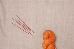 毛线一橙色一束与五根木方形的编织针的在帆布背景 免版税库存照片