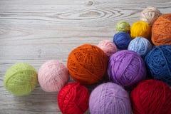 毛线五颜六色的球在桌上的 库存照片