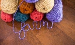 毛线八个丝球与在前景的草书手稿拼写的毛线的 库存照片
