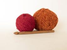 毛线和一个木勾子红色和橙色球在白色backgroun 免版税库存照片