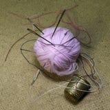 毛线球,针和顶针在桌上 免版税库存图片