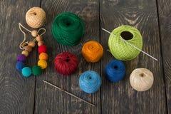 毛线用不同的颜色和工艺的编织的勾子球木表面上 免版税库存照片