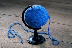 毛线蓝色球在一个立场的地球的 免版税库存照片