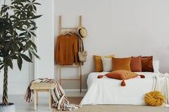 毛线衣、柳条帽子和袋子在木梯子在加长型的床与天鹅绒枕头,拷贝空间旁边在空的墙壁上 免版税库存图片