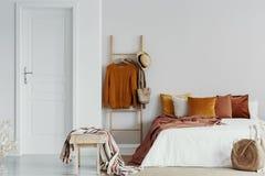 毛线衣、柳条帽子和袋子在木梯子在加长型的床旁边与天鹅绒枕头在白色卧室内部,拷贝空间 免版税库存照片