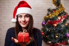 毛线衣和圣诞老人盖帽的年轻美丽的微笑的妇女有一个美国兵的 库存照片
