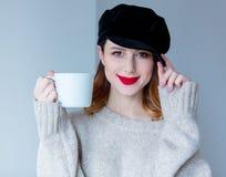毛线衣和帽子的妇女有咖啡的或茶 免版税库存图片