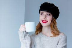 毛线衣和帽子的妇女有咖啡的或茶 库存照片