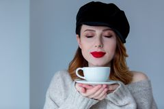 毛线衣和帽子的妇女有咖啡的或茶 免版税库存照片