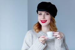 毛线衣和帽子的妇女有咖啡的或茶 免版税图库摄影