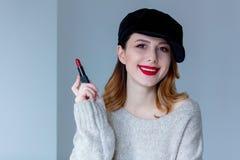 毛线衣和帽子的妇女有唇膏的 库存图片