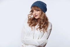 毛线衣和帽子的正面白肤金发的妇女在白色背景 免版税库存图片