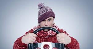 毛线衣和帽子的冻人有方向盘的 概念汽车司机 免版税库存照片