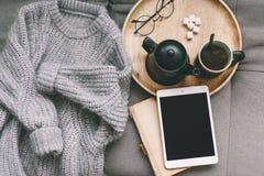 毛线衣和片剂在沙发 图库摄影
