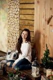 毛线衣和蓝色牛仔裤的年轻美丽的妇女在家坐地板 库存照片