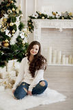 毛线衣和蓝色牛仔裤的年轻美丽的妇女坐地板在圣诞树附近 免版税库存图片