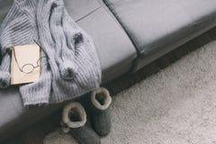 毛线衣和读书在沙发 免版税库存照片