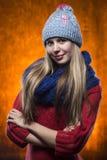 毛线衣的女孩一个盖帽和一条围巾在橙色背景 免版税图库摄影