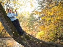 毛线衣的妇女倾斜在树和拍摄使用电话 免版税库存图片