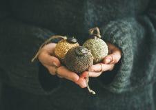 毛线衣的妇女在手上的拿着金黄和银色球 免版税库存照片